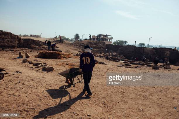 Egyptian men work at an archaeological site near the Valley of the Kings on October 24 2013 The site run in partnership by the Academy of Fine Arts...