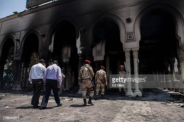 Egyptian Military Police officers walk into the burntout Rabaa alAdaweya Mosque in Nasr City on August 15 2013 in Cairo Egypt An unknown number of...