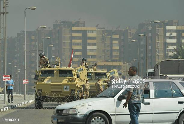 Egyptian military vehicles block a road leading to the Rabaa al-Adawiya protest camp in Cairo as Egyptian police try to disperse supporters of...