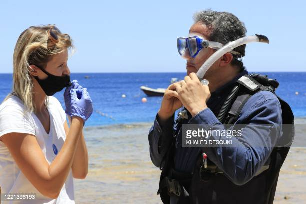 Egyptian Minister of Tourism and Antiquities Khaled alAnani speaks to an employee at a diving center at the Red Sea resort of Sharm elSheikh on June...