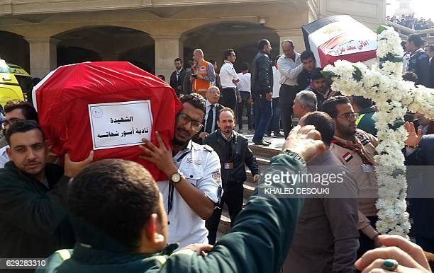 Egyptian mourners and officials carry the coffins of the victims of a bomb explosion that targeted a Coptic Orthodox Church the previous day in Cairo...