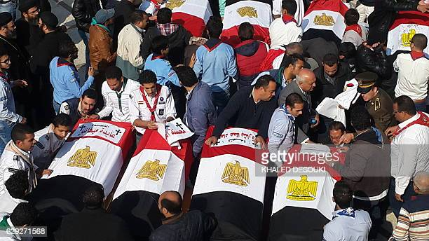 Egyptian mourners and officials stand next to the coffins of the victims of a bomb explosion that targeted a Coptic Orthodox Church the previous day...