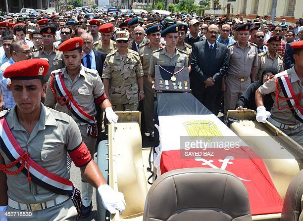 Egyptian mourners and soldiers march along side the coffin of Brigadier General Amro Fathi Saleh AlImara at AlNasr mosque in the Nile Delta town of...