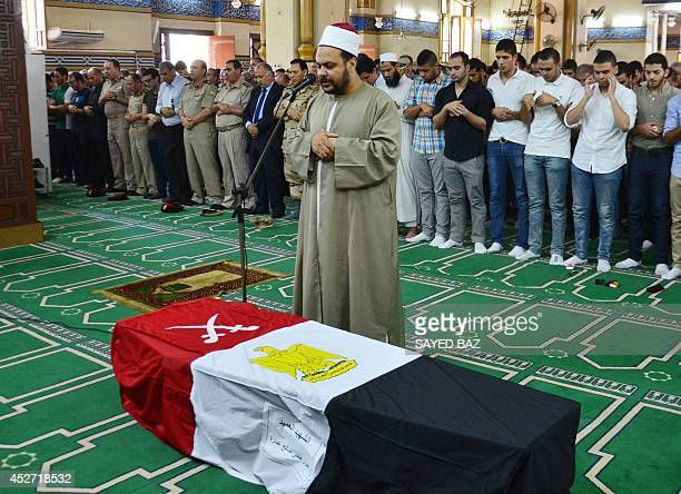 Egyptian mourners pray over the coffin of Brigadier General Amro Fathi Saleh AlImara at AlNasr mosque in the Nile Delta town of Mansura on July 26...
