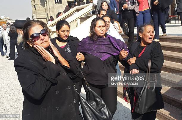 Egyptian mourners react at the end the funeral of the victims of a bomb explosion that targeted a Coptic Orthodox Church the previous day in Cairo on...