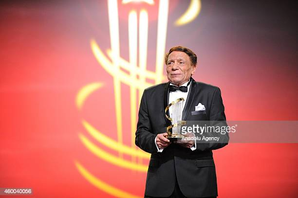 Egyptian movie and stage actor Adel Emam poses with a tribute award during the 14th Marrakech International Film Festival Opening Ceremony on...