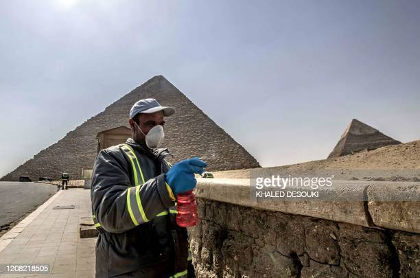 Egyptian municipality workers disinfect the Giza pyramids necropolis on the southwestern outskirts of the Egyptian capital Cairo on March 25 2020 as...
