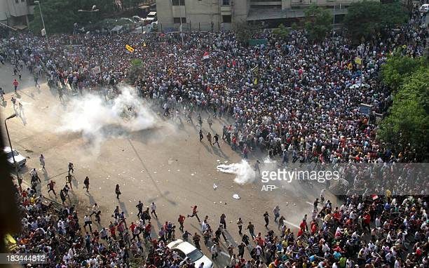 Egyptian Muslim brotherhood and supporters of ousted president Mohamed Morsi run for cover from tear gas during clashes with riot police along Ramsis...