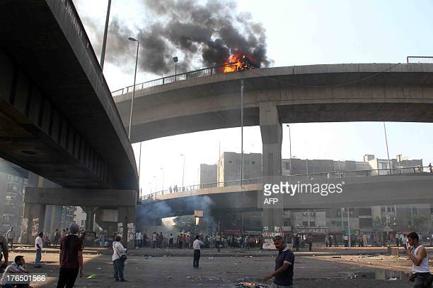 Egyptian Muslim brotherhood supporters of Egypt's ousted president Mohamed Morsi look up at a vehicle burning on six October bridge during clashes...