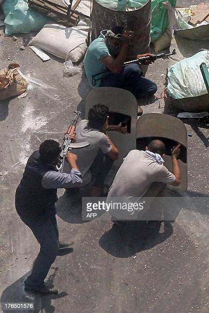 Egyptian Muslim brotherhood supporters of Egypt's ousted president Mohamed Morsi hold AK47 and riot police shields during clashes with riot police at...