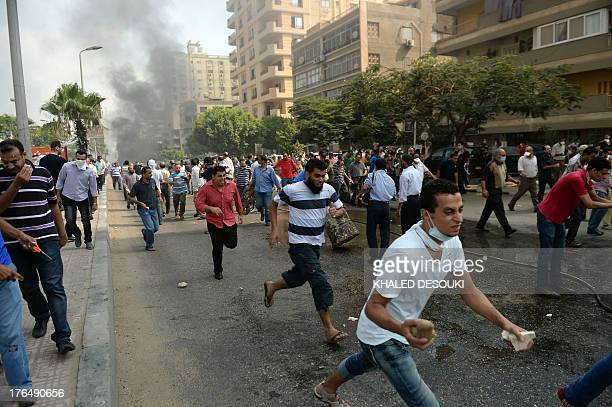 Egyptian Muslim Brotherhood supporters run from police in a street leading to Rabaa al-Adawiya protest camp in Cairo on August 14, 2013. Egypt's...