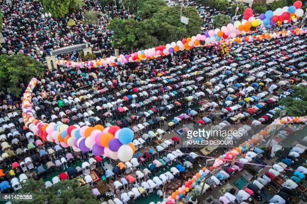 Egyptian Muslim devotees perform the morning Eid al-Adha prayer outside al-Sedik mosque in the northeastern suburb of Sheraton in the capital Cairo,...