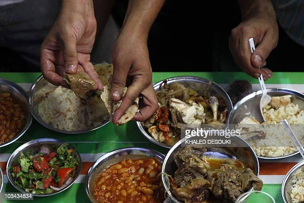 Egyptian Muslims break their daylong Ramadan fast during a group 'Iftar' meal for the residents of a neighbourhood in downtown Cairo on August 18...