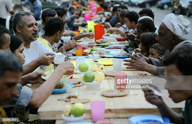 Egyptian Muslims sit on a shared table as they take the Iftar meal to break their daylong fast during the holy month of Ramadan in Cairo 06 October...