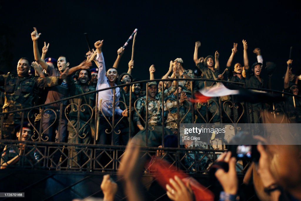 Egyptian opposition protesters and officers of the Egyptian Republican Guard celebrate at the gates of the Republican Guard headquarters in the suburb of Nasr City after a broadcast by the head of the Egyptian military confirming that they will temporarily be taking over from the country's first democratically elected president Mohammed Morsi on July 3, 2013 in Cairo, Egypt. As unrest spreads throughout the country, at least 23 people were killed in Cairo on Tuesday and over 200 others were injured. It has been reported that the military has taken over the state television.