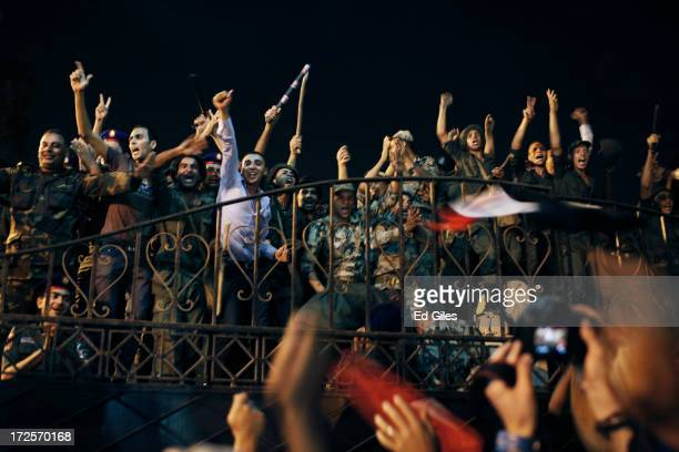 Egyptian opposition protesters and officers of the Egyptian Republican Guard celebrate at the gates of the Republican Guard headquarters in the...