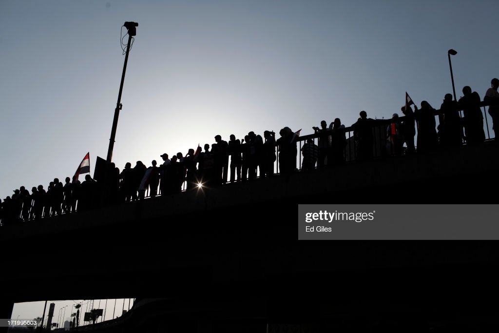 Egyptian opposition protesters stand on a bridge during a demonstration in Tahrir Square as part of the 'Tamarod' campaign on June 30, 2013 in Cairo, Egypt. Crowds of pro- and anti-Morsi protesters gathered in locations across Egypt on June 30, the day of a series of nation-wide mass demonstrations entitled 'Tamarod', or 'Rebel', planned to take place on the first anniversary of Morsi's election to the Egyptian Presidency. The 'Tamarod' campaign, organised by a coalition of opposition political groups, aims to bring down the government of President Morsi through country-wide demonstrations. (Photo by Ed Giles/Getty Images).