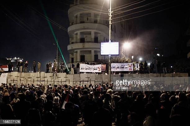 Egyptian opposition stand on top of a concrete wall built by Egyptian security forces in previous days outside Egypt's Presidential Palace during a...