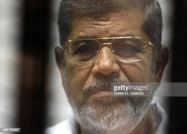 Egyptian ousted Islamist president Mohamed Morsi looks on from behind the defendants cage during is trial on May 8 2014 alongside 130 others on...