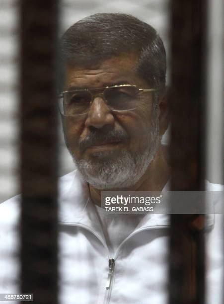 Egyptian ousted Islamist president Mohamed Morsi looks on from behind the defendants cage during is trial on May 8, 2014 alongside 130 others on...