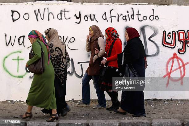 Egyptian people walk past graffiti written on the walls in Mohammed Mahmoud Street off Tahrir Square on January 26 2012 in Cairo Egypt Tens of...
