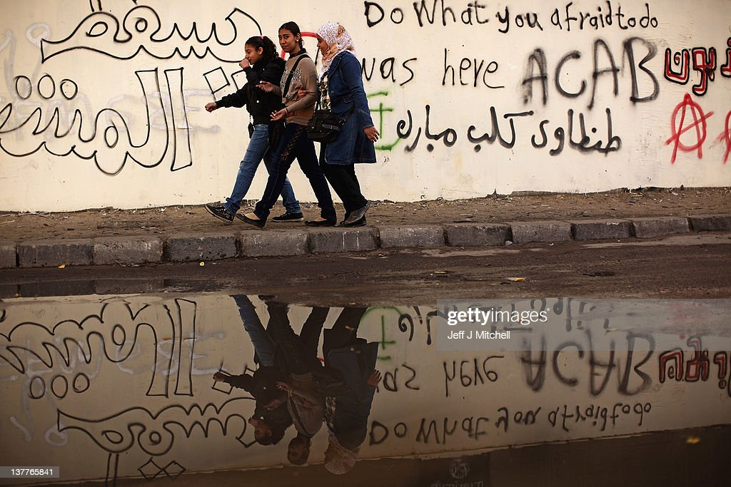 Egyptian people walk past graffiti written on the walls in Mohammed Mahmoud Street off Tahrir Square on January 26, 2012 in Cairo, Egypt. Tens of thousands of Egyptian people gathered yesterday to celebrate the anniversary of the start of the uprising which ended President Hosni Mubaraks rule.
