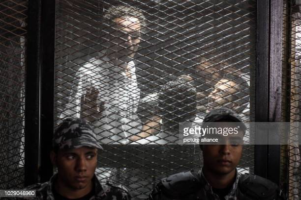 Egyptian photojournalist Mahmoud Abu Zeid also known as 'Shawkan' stands in the defendants cage after a verdict sentenced him to five years during...