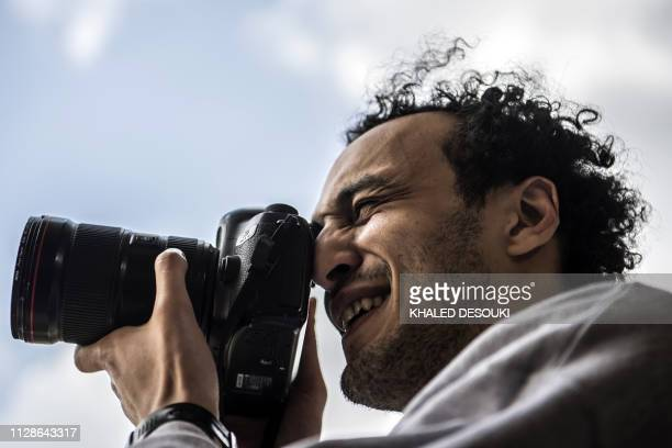 Egyptian photojournalist Mahmoud Abu Zeid widely known as Shawkan carries a camera at his home in the capital Cairo on March 4 2019 The awardwinning...