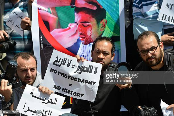 Egyptian photojournalists hold signs in English and Arabic including one reading 'Freedom to the camera' during a demonstration outside the Shura...