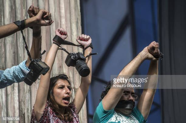 Egyptian photojournalists raise their cameras during a demonstration outside the Syndicate headquarters in Cairo on May 3 2016 on the occasion of...