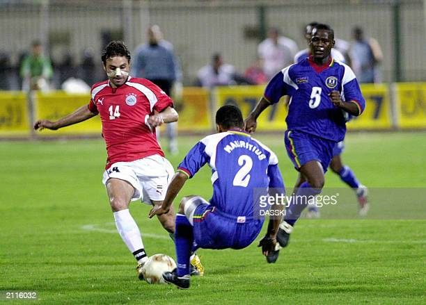 Egyptian player Hazem Emam tries to make his way between Mauritius' players Edward Geuolano and Robert Rako during their African Nations Cup Group 10...