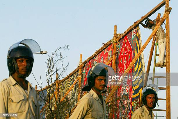 Egyptian police erect cloth panels around the destroyed Ghazala Gardens Hotel July 23 2005 at the Egyptian Red Sea resort of Sharm elSheikh July 23...