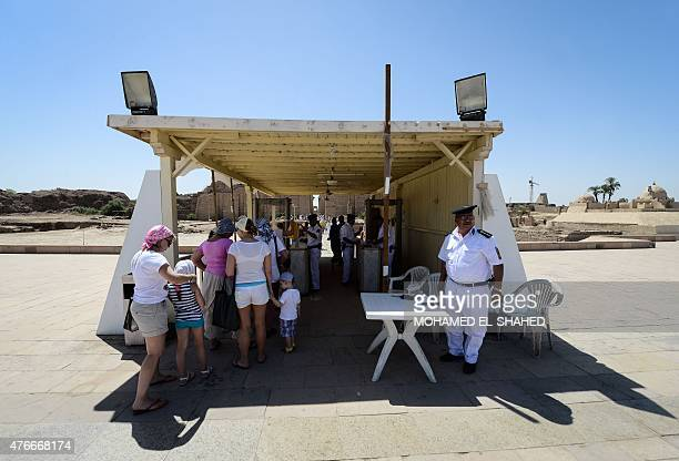 Egyptian police man a security check as tourists enter Karnak temple in Luxor a town 700 kilometres south of the Egyptian capital Cairo on June 11...