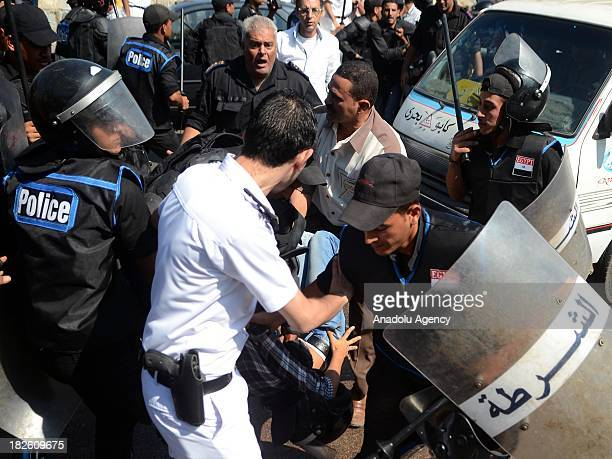 Egyptian police officers detain a supporter of 28-year-old Khaled Said who died following police questioning in 2010, during clashes with police...