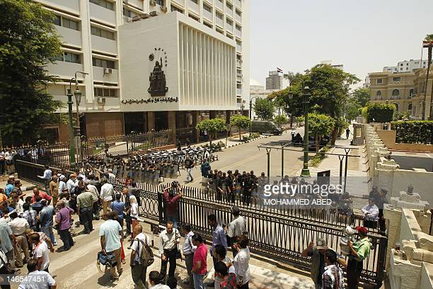 Egyptian policemen block the closed road in front of the parliament building to prevent members of the recentlyscrapped legistlature from entering...