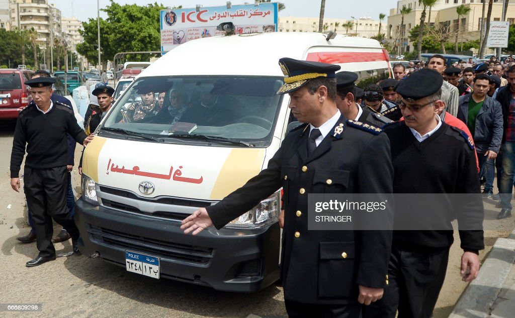 Egyptian policemen make way for the ambulance transporting the coffin of policewoman Brigadier Nagwa el-Haggar during her funeral on April 10, 2017, after she died during a blast that struck outside the Coptic Orthodox Patriarchate headquarters in the Mediterranean city of Alexandria on Palm Sunday the day before. Egypt prepared to impose a state of emergency after jihadist bombings killed dozens at two churches in the deadliest attacks in recent memory on the country's Coptic Christian minority. /