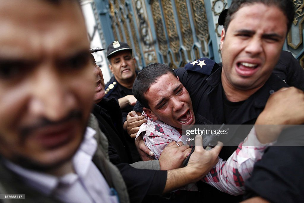 Egyptian policemen protect an opposition demonstrater after a scuffle with members of the Muslim Brotherhood and supporters of Egypt's Islamist President Mohamed Morsi during clashes outside the presidential palace in Cairo on December 5, 2012. Supporters of Egypt's Islamist President Mohamed Morsi tore down tents and forced opposition protesters to flee the presidential palace on Wednesday, as his deputy said a vote on a disputed constitution would go ahead in 10 days.