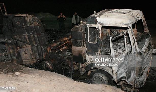 Egyptian policemen stand at the site of a burnedout truck which was struck when a French transport aircraft used by the Multinational Force and...