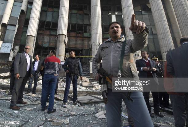 Egyptian policemen stand outside the court in the working class Imbaba neighbourhood of Cairo on January 14 2014 after blast hit the building two...