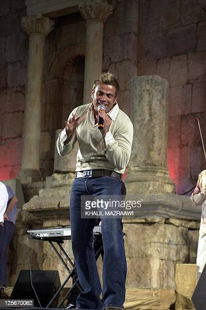 Egyptian pop star Amro Diab performs at the southern theatre in Jarash where some 3500 fans attended his concert 01 August 2003 AFP PHOTO/Khalil...