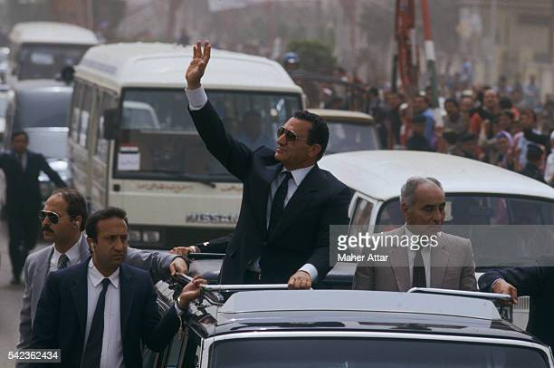 Egyptian president and candidate for reelection Hosni Mubarak waves from an open vehicle in the streets of his home town Mansourah 150 kilometres...
