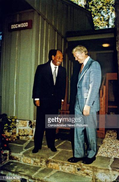 Egyptian President Anwar Al Sadat and US President Jimmy Carter share a smile as they talk together during the EgyptianIsraeli peace negotiations...