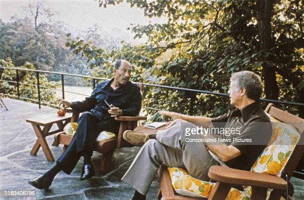 Egyptian President Anwar Al Sadat and US President Jimmy Carter talk together during the EgyptianIsraeli peace negotiations on the porch of Aspen...