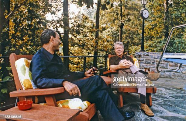 Egyptian President Anwar Al Sadat and US President Jimmy Carter talk together during the Egyptian-Israeli peace negotiations, on the porch of Aspen...