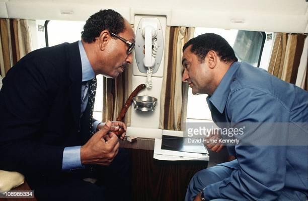 Egyptian president Anwar al Sadat leans in to speak with Vice President Hosni Mubarak while they travel from Cairo to Alexandria in the Egyptian...