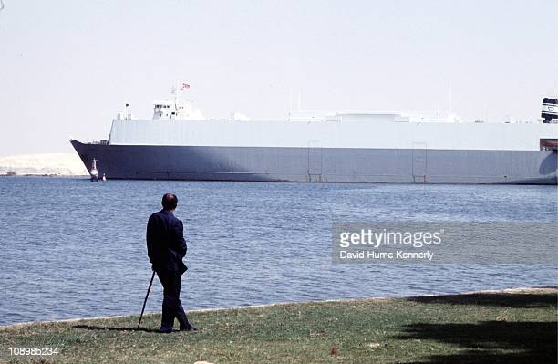 Egyptian president Anwar al Sadat looks out upon a Norwegian ship traveling on the Suez Canal outside the presidential rest house located in the Suez...