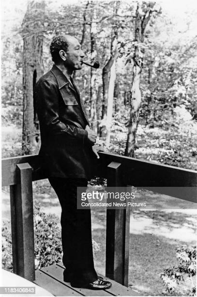 Egyptian President Anwar Al Sadat smokes his pipe during the EgyptianIsraeli peace negotiations at Camp David outside of Dogwood Cottage at Camp...