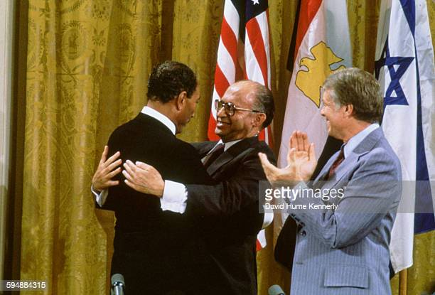 Egyptian President Anwar alSadat and Israeli Premier Menachem Begin embrace while US President Jimmy Carter applauds after signing the Camp David...