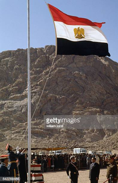 Egyptian President Anwar alSadat raises the Egyptian flag near St Catherine's Monastery at the foot of Mount Sinai part of which was recently handed...