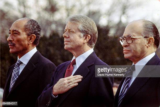 Egyptian President Anwar alSadat US President Jimmy Carter and Israeli Premier Menachem Begin listen to the national anthem before signing the...